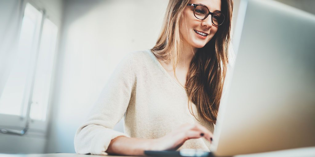 woman smiling working on computer